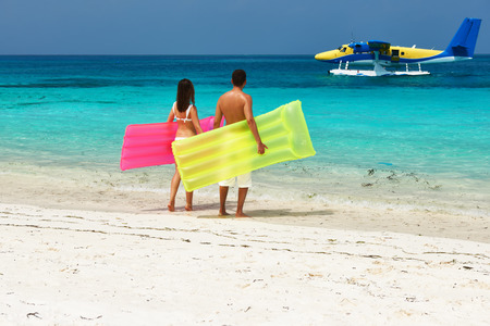 Couple with inflatable rafts looking at arrived seaplane on a tropical beach at Maldives. No brand names or copyright objects photo