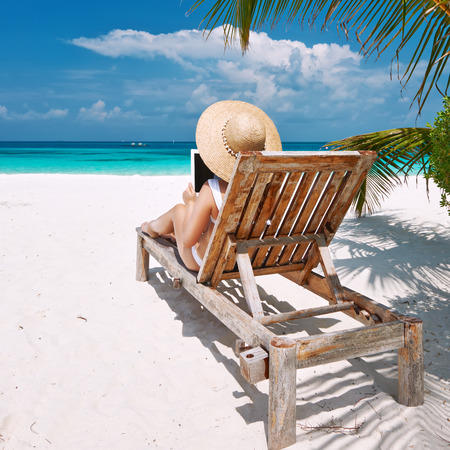 Young woman in hat with tablet pc at the beach photo