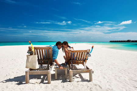 Couple relax on a tropical beach at Maldives photo