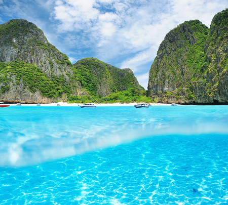 Beautiful lagoon at  Phi Phi Ley island with white sand bottom underwater and above water split view photo