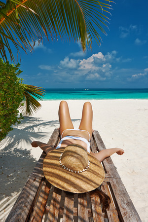 Woman at beautiful beach lying on chaise lounge photo