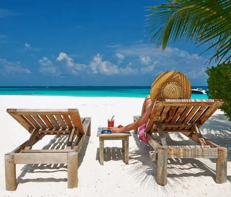 Woman at beautiful beach with chaise-lounges Stock Photo