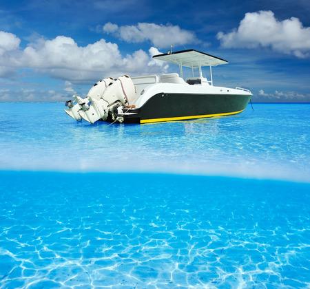 Mooi strand en motorboot met wit zand bodem onder water en boven water split view
