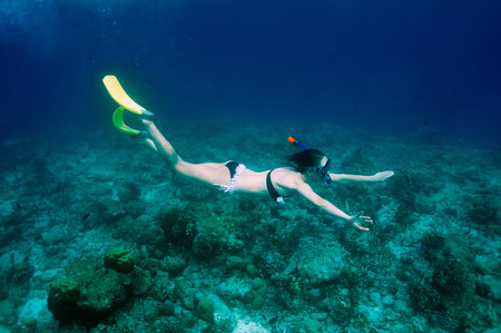 Woman with mask snorkeling in clear water  photo