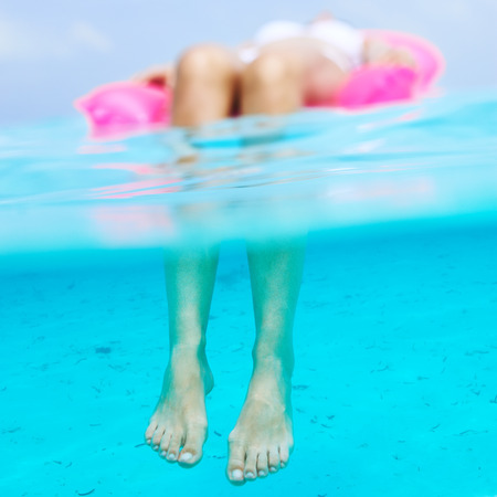 Woman relaxing on inflatable mattress at the beach, view from underwater photo