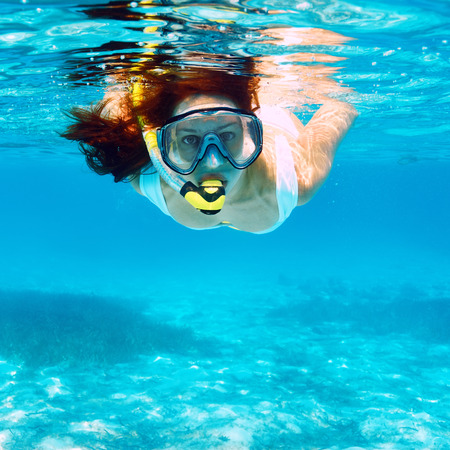 Woman with mask snorkeling in clear water  Stock Photo