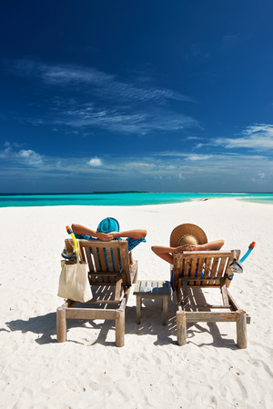people sitting on chair: Couple relax on a tropical beach at Maldives