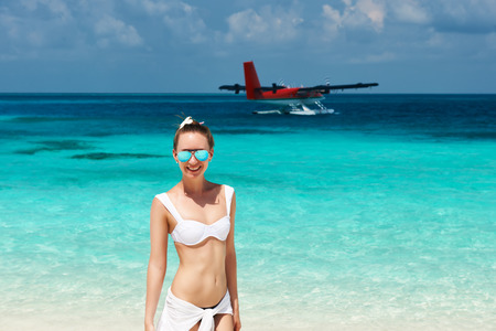 Woman in bikini at tropical beach. Seaplane at background. photo