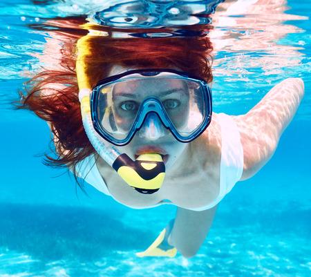 Vrouw met masker snorkelen in helder water Stockfoto