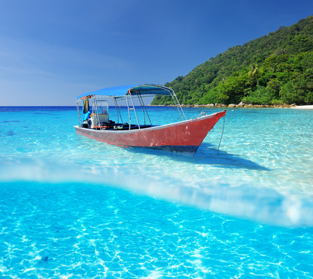 Beautiful beach and motor boat with white sand bottom underwater and above water split view photo
