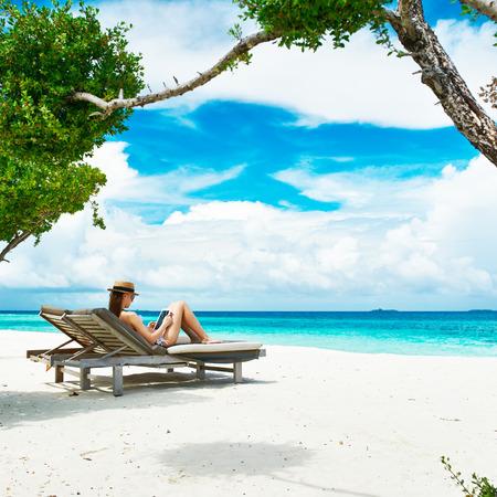 Junge Frau im Hut mit Tablet PC am Strand