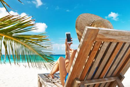 Jonge vrouw in de hoed met de mobiele telefoon op het strand Stockfoto