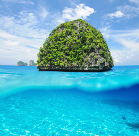 Beautiful uninhabited island in Thailand with white sand bottom underwater and above water split view photo