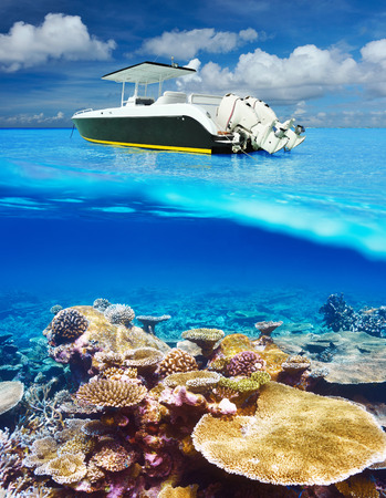nautical vessels: Beautiful beach and motor boat with coral reef bottom underwater and above water split view