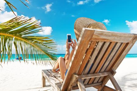 Junge Frau im Hut mit Handy am Strand