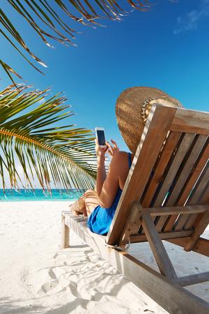 Jonge vrouw in hoed met mobiele telefoon op het strand Stockfoto