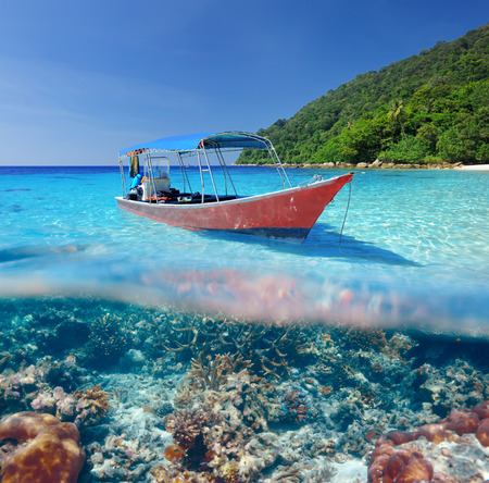 beach cruiser: Beautiful beach and motor boat with coral reef bottom underwater and above water split view