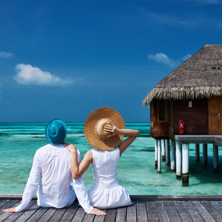 tropical beach: Couple on a tropical beach jetty at Maldives Stock Photo