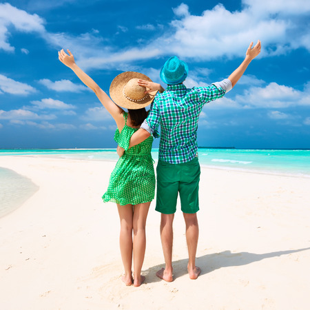 green back: Couple in green on a tropical beach at Maldives