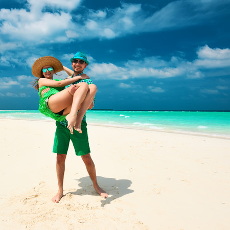 Couple in green on a tropical beach at Maldives. Man in holding woman on his arms. photo