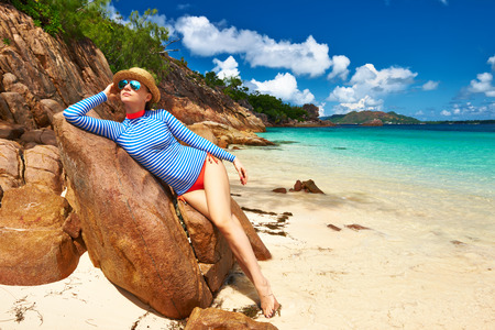 Woman at beautiful beach wearing rash guard. Seychelles, Curieuse island photo