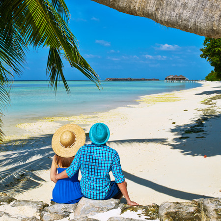Couple in blue clothes on a tropical beach at Maldives photo