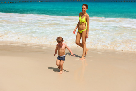 Two year old baby boy and his mother playing on beach at Seychelles photo