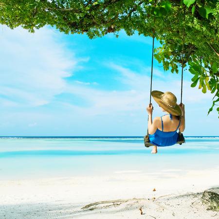 columpio: Mujer en azul balanceo vestido en la playa tropical