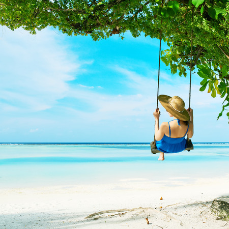 Woman in blue dress swinging at tropical beach Stock Photo