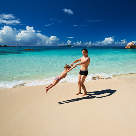 two year old: Two year old baby boy and his father playing on beach at Seychelles Stock Photo