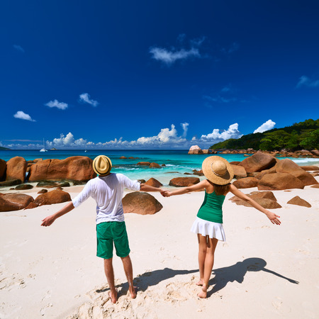 Couple in green on a tropical beach at Seychelles photo