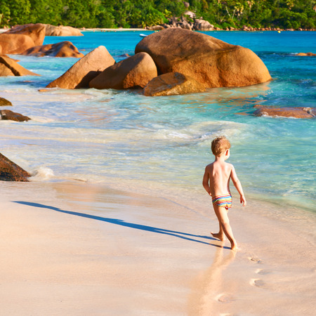 Two year old baby boy playing on beach at Seychelles photo