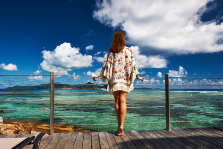 pareo: Woman on a tropical beach jetty at at Seychelles, La Digue.