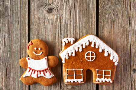 Christmas homemade gingerbread girl and house on wooden table photo
