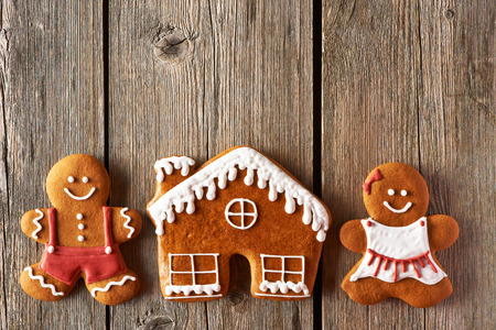 gingerbread house: Christmas homemade gingerbread couple and house on wooden table