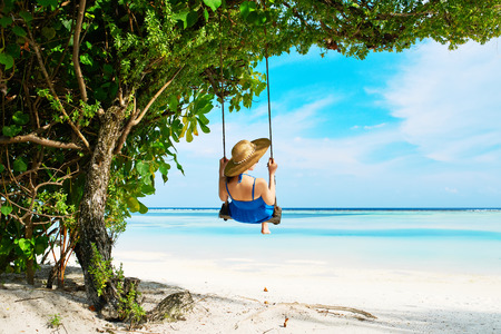 Woman in blue dress swinging at tropical beach photo