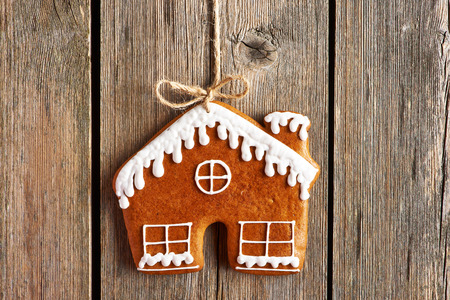 Christmas homemade gingerbread house cookie over wooden background photo
