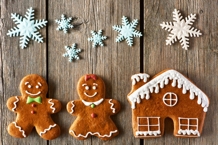 Christmas homemade gingerbread couple and house on wooden table photo