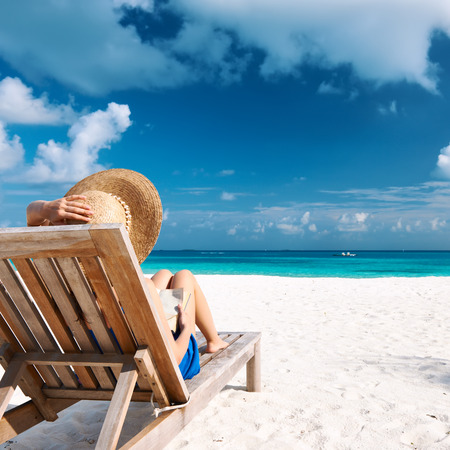 playas tropicales: Mujer joven que lee un libro en la playa