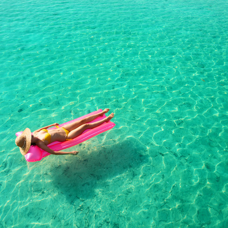 Woman relaxing on inflatable mattress at the beach photo