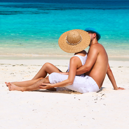 Couple in white relax on a tropical beach at Maldives photo