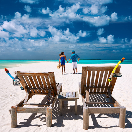 Couple running on a tropical beach at Maldives photo