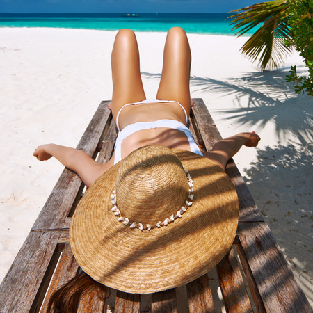 chaise lounge: Woman at beautiful beach lying on chaise lounge