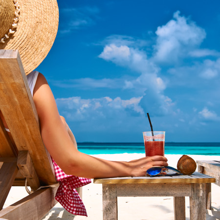 drink at the beach: Woman at beautiful beach with chaise-lounges Stock Photo