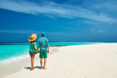 travel destinations: Couple in green on a tropical beach at Maldives