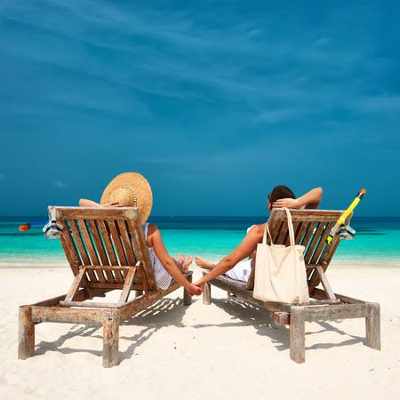 playa vacaciones: Pareja en blanco relajarse en una playa tropical en Maldivas Foto de archivo