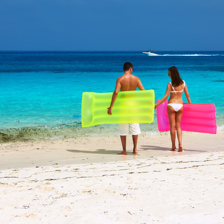 Couple with inflatable rafts on a tropical beach at Maldives photo