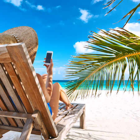 white sand: Young woman in hat with mobile phone at the beach Stock Photo