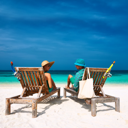 Couple in green relax on a tropical beach at Maldives photo