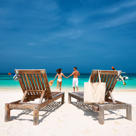 Couple in white running on a tropical beach at Maldives photo